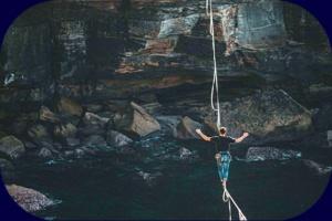 Mann balanciert auf Seil